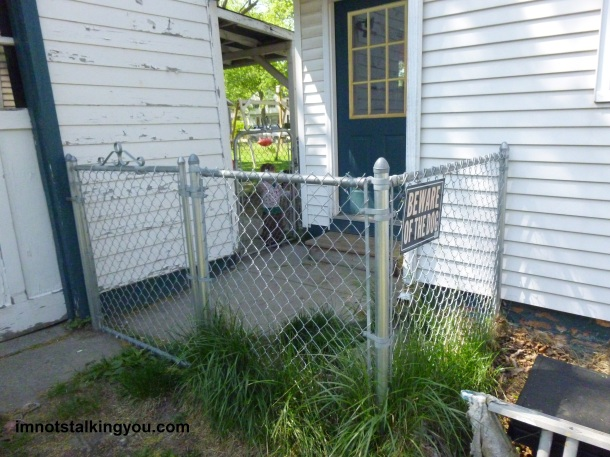 The newest part of the fence, enclosing the backdoor.  See old fence restricting a toddler in the background.
